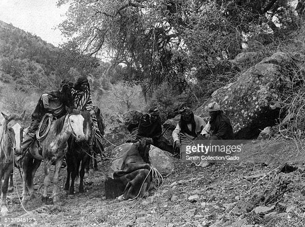 Photograph of a group of Native American men sitting on the ground in the desert their horses standing to the left titled 'Apaches a story telling...