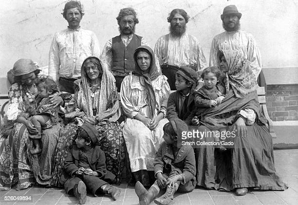 A photograph of a group of Romani people from Hungary the group consists of men women and young children the women are seated and all wear...