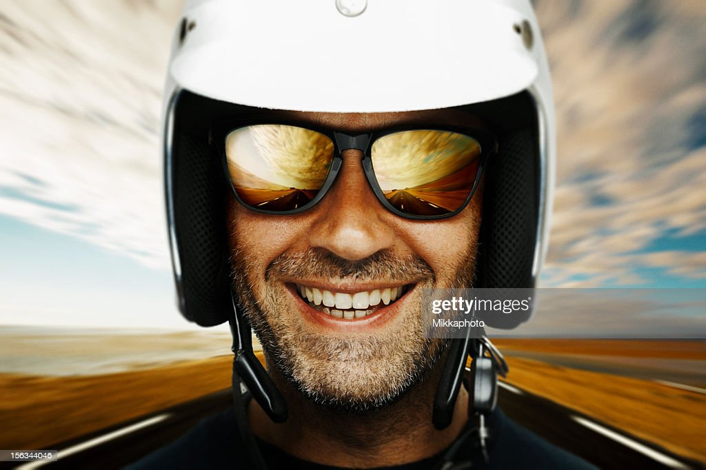 Photograph of a happy male biker smiling with sky backdrop : Stock Photo