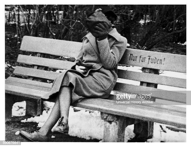 """Photograph of a Jewish woman in Austria sitting on a bench marked """"Only for Jews"""" Dated 1938"""