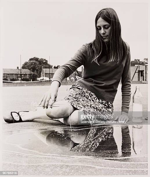 A photograph of a King�s Lynn schoolgirl adding water to a puddle to check for evaporation levels as part of a school science experiment taken by...
