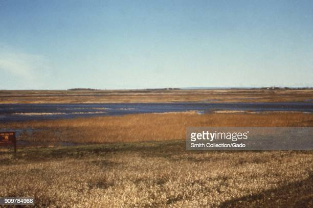 Photograph of a landscape consisting of a river with reed and grassland around clear blue sky above and a sign at J Clark Salyer National Wildlife...