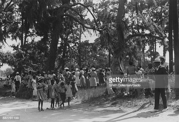 Photograph of a large group of people gathered for a Fourth of July celebration, the group consists of men, women and children, everyone is dressed...
