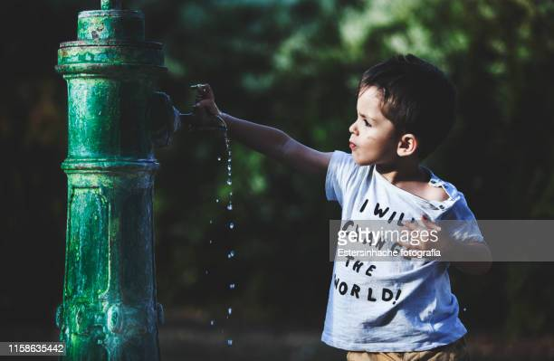 photograph of a little boy drinking water from an old fountain - eau potable photos et images de collection