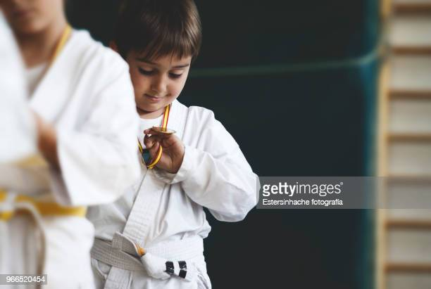 photograph of a little boy looking happy at a medal won practicing karate - judo stock pictures, royalty-free photos & images