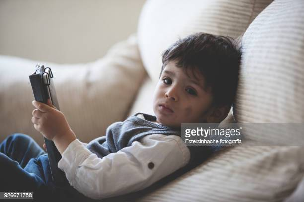 Photograph of a little boy playing with a digital tablet