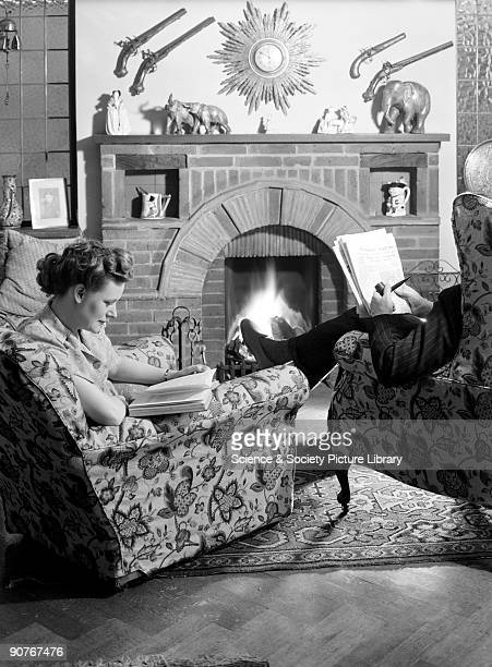 A photograph of a man and a women sitting in armchairs to read in front of a fire This photograph was taken by Photographic Advertising Limited in...