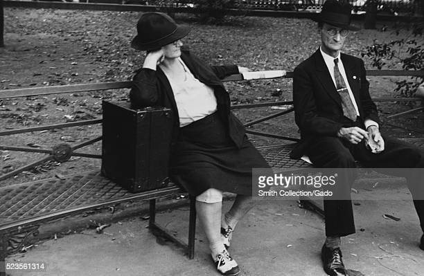 A photograph of a man and woman sitting on a metal park bench the woman wears a jacket skirt and hat she is leaning on a large black case the man is...