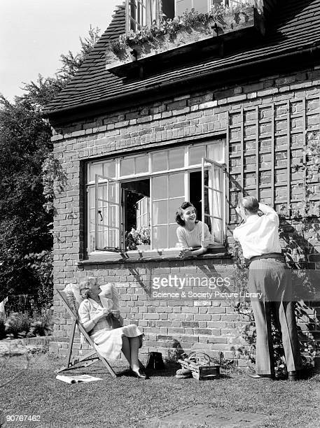 A photograph of a man fixing a garden trellis taken by Photographic Advertising Limited in about 1950 Meanwhile one woman leans out of a window to...