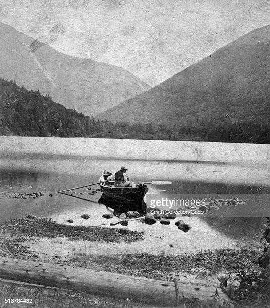 Photograph of a man in a canoe in shallow water mountains in the background titled 'Echo Lake and Franconia Notch White Mountains' published by Paul...