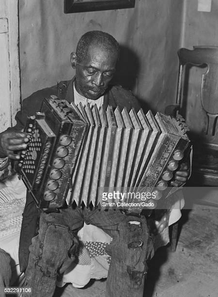 A photograph of a man named John Dyson sitting on the edge of a bed and playing an accordion he was a borrower from the Farm Security Administration...
