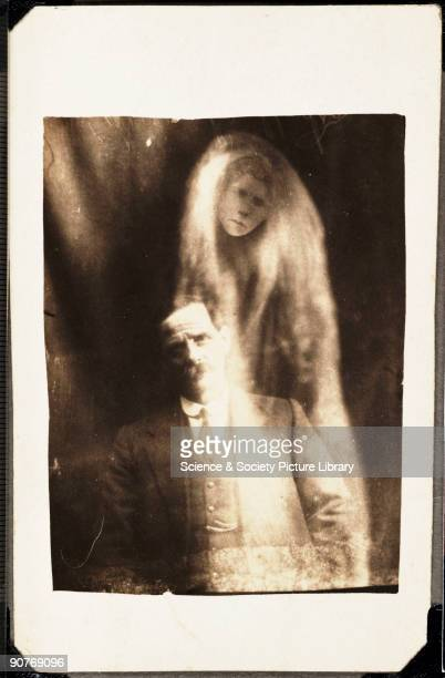 A photograph of a man taken by William Hope A woman's face appears in 'misty' drapes around the man He was said to have been asked to sit for a...