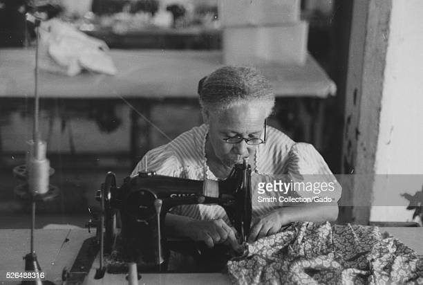 A photograph of a mature Puerto Rican woman using a sewing machine in the Everglades Needlework Factory she is using the machine to work a piece of...
