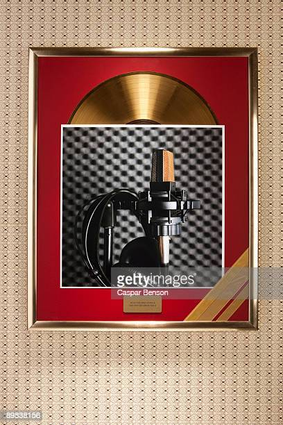 A photograph of a microphone and headphones on top of a framed gold record
