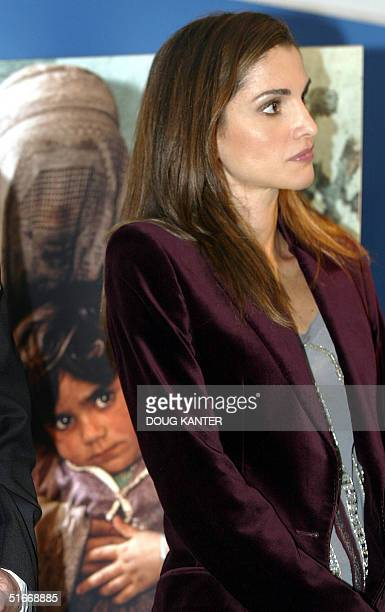 A photograph of a mother and child from Afghanistan stands behind Queen Rania AlAbdullah of Jordan at the Steuben Gallery in New York 12 November...