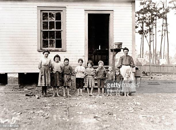 Photograph of a mother and her nine children, five of whom work with her in a Georgia USA cotton mill, taken by American sociologist and photographer...