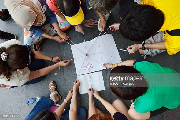 Photograph of a multiracial group of people trying to achieve something collectively. Shot in Sentosa Island, Singapore.