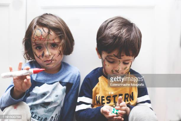 photograph of a naughty boy and girl who have painted their face with a marker pen - travessura imagens e fotografias de stock