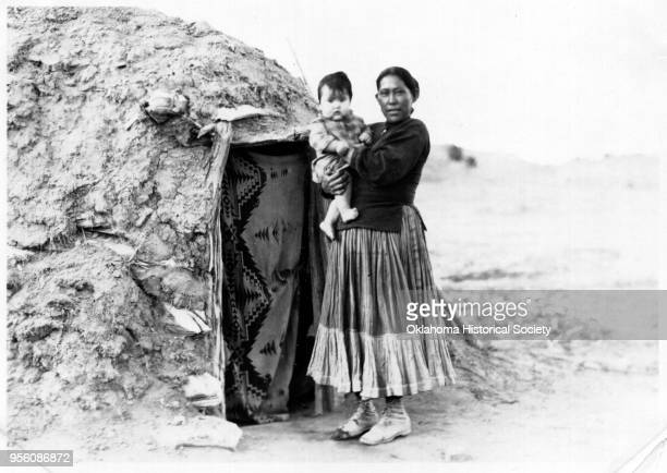 Photograph of a Navajo woman holding a child in front of a hogan early twentieth century There is a woven wool blanket covering the door