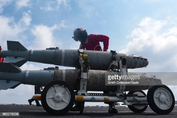 Photograph of a navy sailor transporting a bomb on the flight deck of the Nimitz-class aircraft carrier USS Harry S Truman, May 13, 2018.