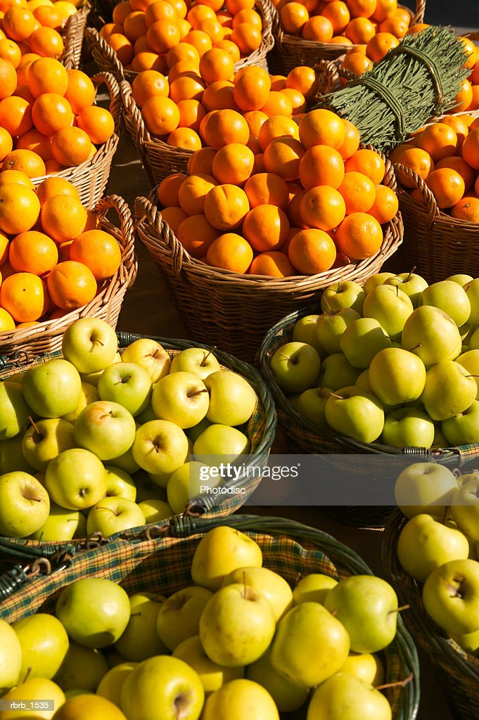 photograph of a number of baskets of both apples and oranges : Stock Photo