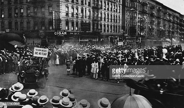 A photograph of a parade organized by the United Negro Improvement Association UNIA a large crowd is gathered in the streets leaving room for cars to...