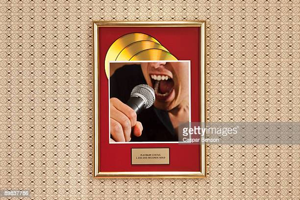 A photograph of a person singing on top of a framed gold record