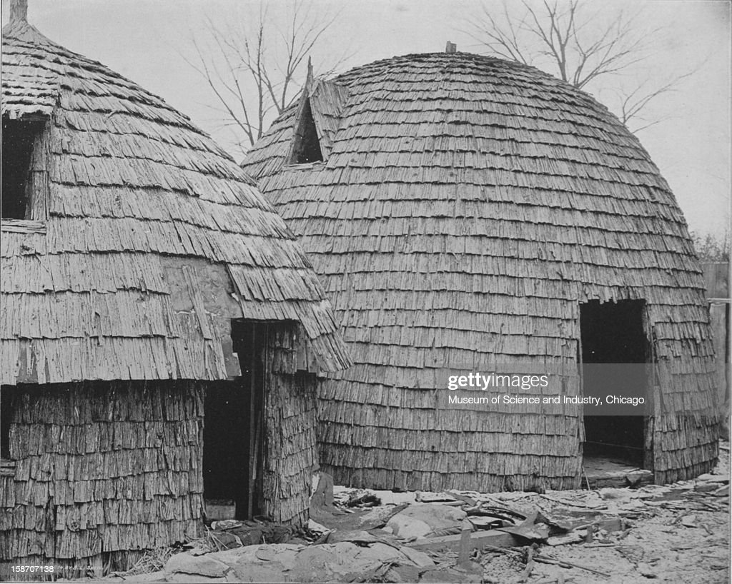 A photograph of a reproduction of Huts used in the African Wilds at the World's Columbian Exposition in Chicago, Illinois, 1893. This image was published in the 'Portfolio of Photographs of the World's Fair-Art Series No.16,' by the Werner Company, 1893-1894.