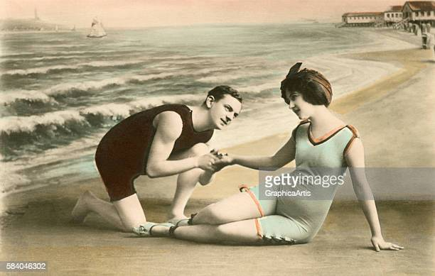 Photograph of a romantic Victorian couple in bathing suits holding hands at the beach 1911 Handcolored silver print