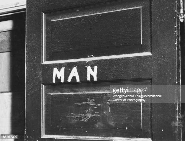 Photograph of a sign reading 'Man' painted on a door possibly signalling the women's bathroom New York ca1940s Photo by Weegee/International Center...