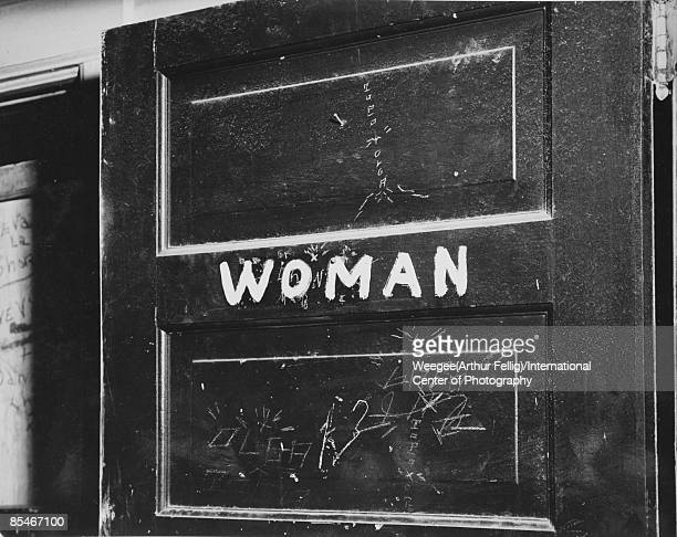 Photograph of a sign reading 'Woman' painted on a door possibly signalling the women's bathroom New York ca1940s Photo by Weegee/International Center...