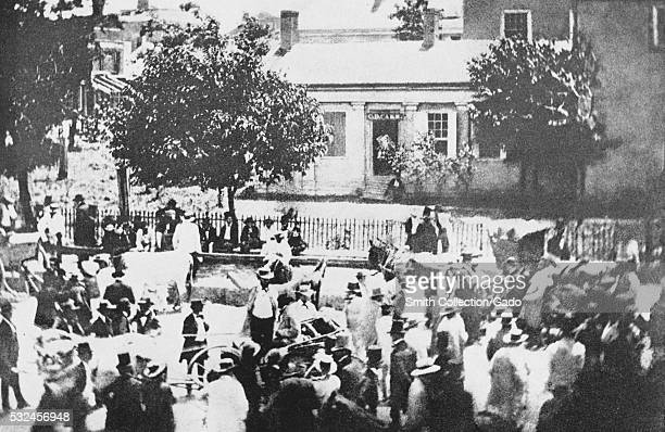 A photograph of a slave auction being held in a public space the crowd consists of men most of whom are wearing suits and hats an auctioneer...
