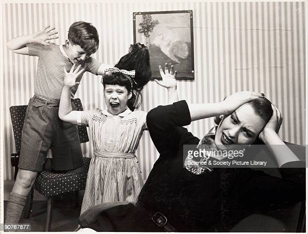 A photograph of a stressed mother unable to control her children who are fighting with each other taken by Photographic Advertising Limited in 1959...