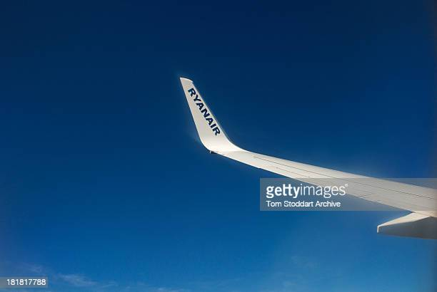 A photograph of a wing of a Ryanair plane flying in the blue sky towards Stansted Airport in Essex England Ryanair was founded in 1985 in Dublin...