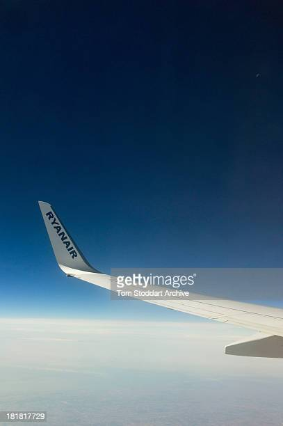 A photograph of a wing of a Ryanair plane flying over the clouds in the blue sky towards Stansted Airport in Essex England Ryanair was founded in...