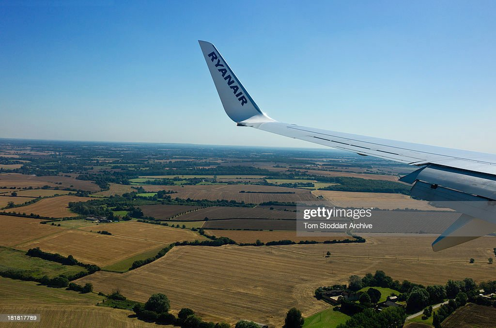 A photograph of a wing of a Ryanair plane flying over the English country side towards Stansted Airport in Essex, England. Ryanair was founded in 1985 in Dublin, Ireland. Its CEO Michael O'Leary has created one of the biggest and most successful budget airlines in the world over the last 27 years which carries over 70 million passengers per year.