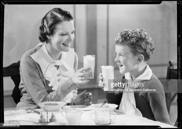 Photograph of a woman and a boy sitting at a dining table holding glasses of milk Southern California 1933