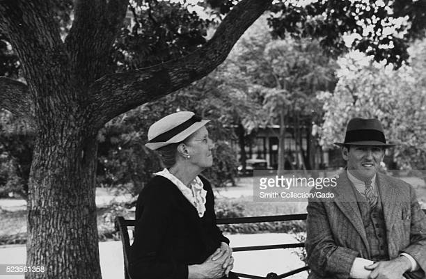 A photograph of a woman and a man sitting on a metal park bench the woman is wearing a dark dress and a hat the man is wearing a grey suit and tie...