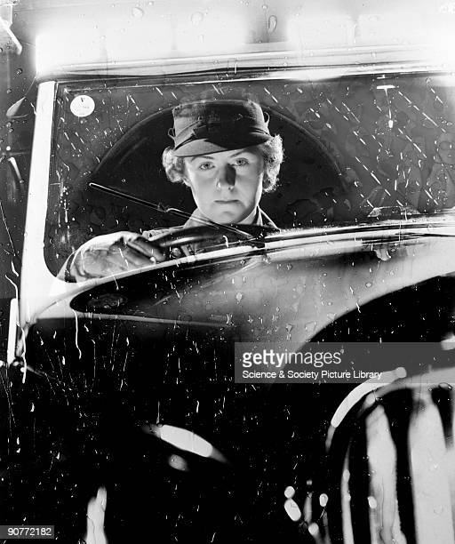 A photograph of a woman driving a car in the rain taken by Photographic Advertising Limited in about 1950 This atmospheric yet staged photograph was...