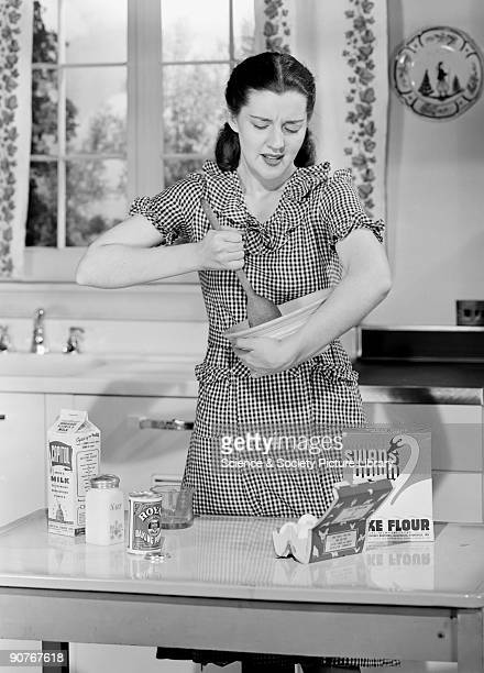 A photograph of a woman mixing ingredients in a bowl with a large wooden spoon taken by Photographic Advertising Limited in the studio kitchen The...