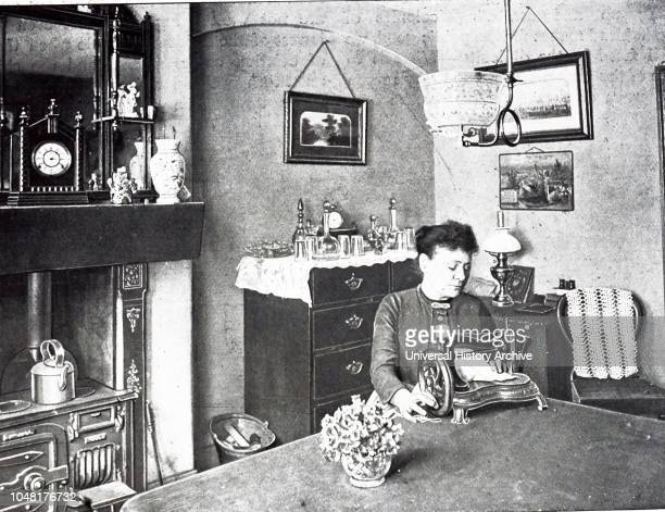 A photograph of a woman using her sewing machine in the new room of her model dwelling Dated 19th century