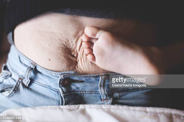 Photograph of a woman's belly after giving birth, next to the barefoot of her son