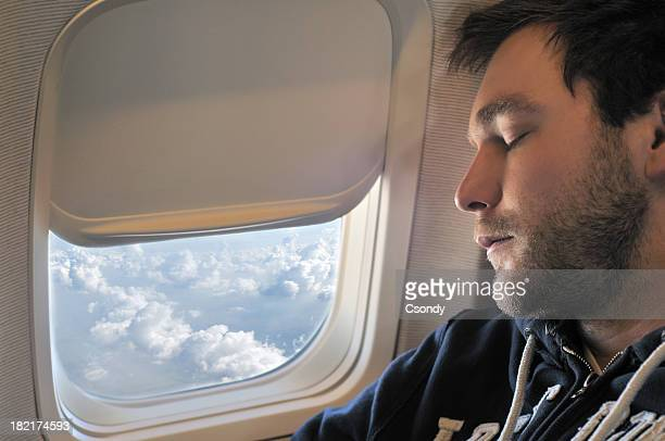Photograph of a young man sleeping on plane in flight