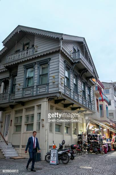 Photograph of a younger man in a business suit walking on a cobbled street near a street market Istanbul Turkey November 15 2017