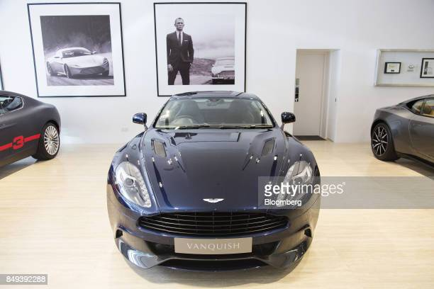 A photograph of actor Daniel Craig as James Bond is displayed on a wall behind an Aston Martin Vanquish luxury automobile on display at an Aston...