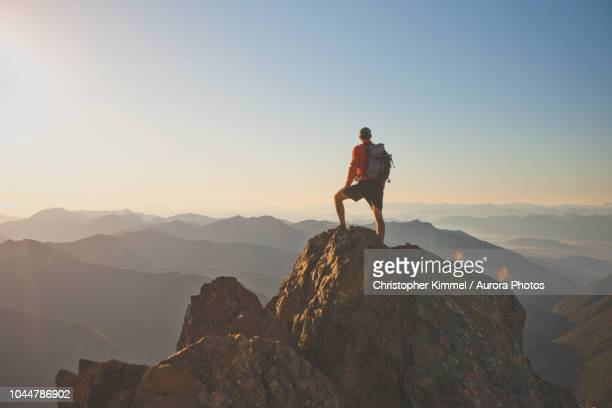 photograph of adventurous backpacker standing on mountain peak, north cascades national park, washington state, usa - berg stock-fotos und bilder