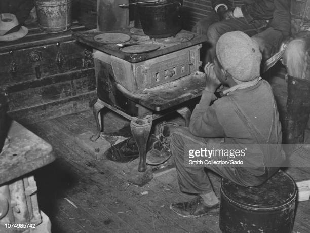 Photograph of African American boy trying to warm up by the stove on a cold strawberry picking season Independence Louisiana April 1939 From the New...