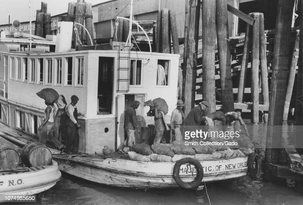 Photograph of African American men unloading heavy sacks with oysters from a packet boat to dock New Orleans Louisiana 1935 From the New York Public...