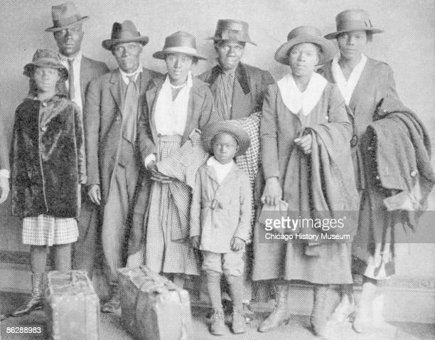 Photograph of African American men women and children who participated in the Great Migration to the north with suitcases and luggage placed in front...