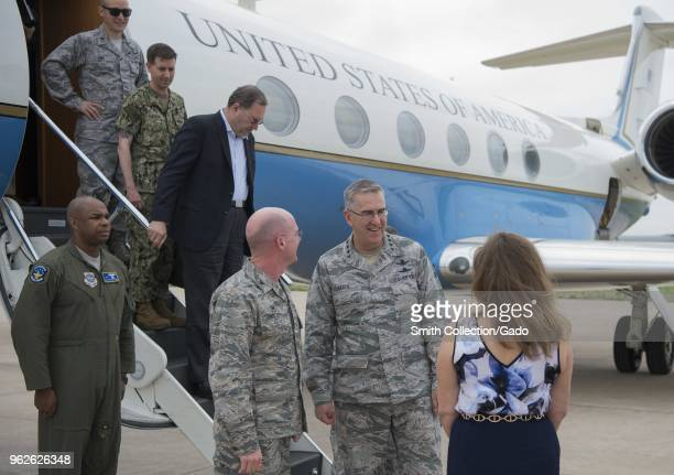 Photograph of air force officers including General John E Hyten and Colonel Troy L Endicott and Tammy Endicott greeting one another outside of a...